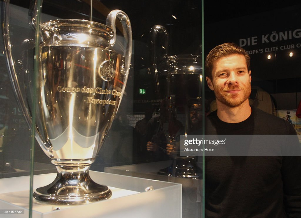 FC Bayern Muenchen player Xabi Alonso stands next to the Champions League trophy during his visit at the FC Bayern Erlebniswelt museum at Allianz Arena on October 14, 2014 in Munich, Germany.