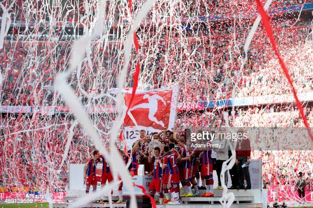Bayern Muenchen players celebrate with the Bundesliga championship trophy after the Bundesliga match between Bayern Muenchen and VfB Stuttgart at...