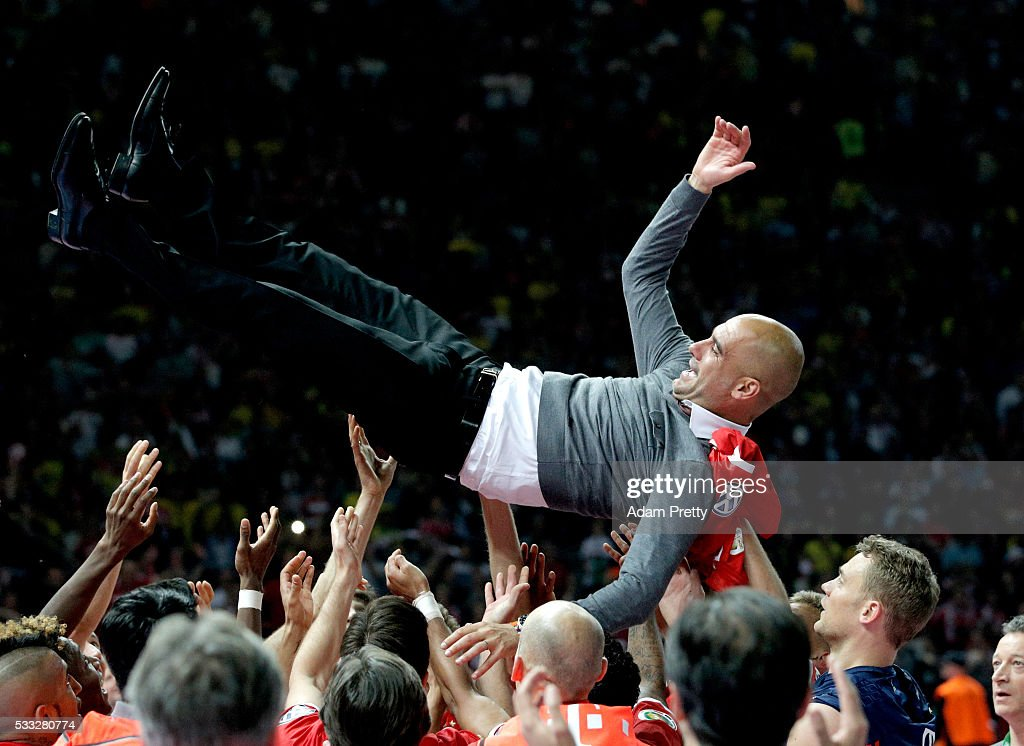 Bayern Muenchen players lift head coach Josep Guardiola after winning the DFB Cup Final between Bayern Muenchen and Borussia Dortmund at Olympiastadion on May 21, 2016 in Berlin, Germany.