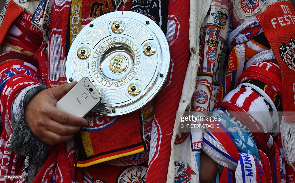 A Bayern Munich supporter holds a model of the German football Championship trophy ahead the German first division Bundesliga football match Bayern Munich vs Borussia Moenchengladbach in Munich, southern Germany, on April 30, 2016. / AFP / CHRISTOF
