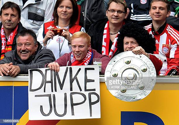 Bayern Munich supporters hold up a poster reading 'Thank You Jupp' and a mockup of the German League Bundesliga trophy during the German first...