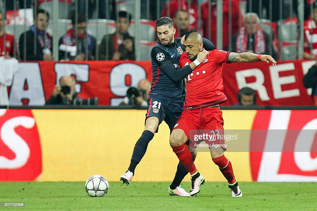 Bayern Munich's Arturo Vidal (R) and Yannick Carrasco of Atletico Madrid (L) vie for the ball during the UEFA Champions League semifinal second leg soccer match between FC Bayern Munich and Atletico Madrid at the Allianz Arena in Munich, Germany on May 3, 2016.