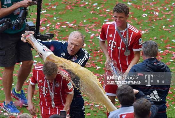 Bayern Munich's assistant coach Hermann Gerland pours beer over Bayern Munich's defender Philipp Lahm after the German first division Bundesliga...