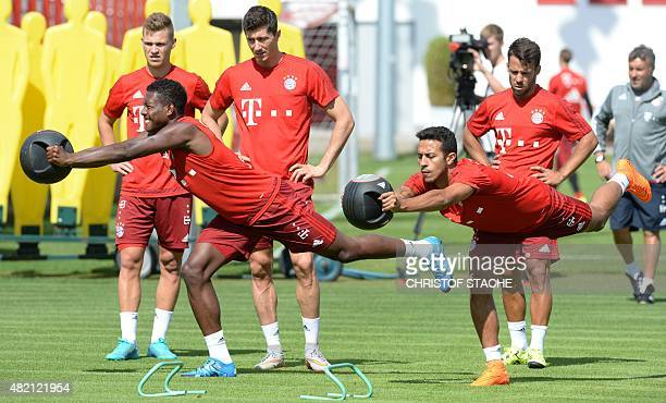 Bayern Munich's Austrian defender David Alaba and Bayern Munich's Spanish midfielder Thiago Alcantara stretch during a training session of the German...