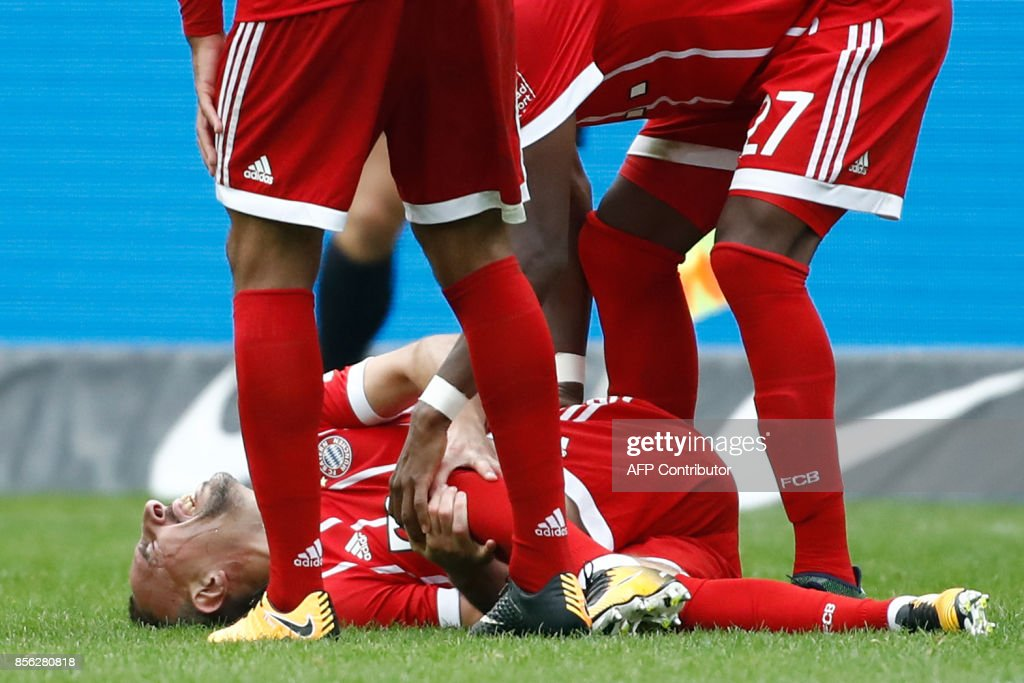 Bayern Munich's Austrian defender David Alaba (R) and Bayern Munich's French midfielder Corentin Tolisso check on their tgeammate French midfielder Franck Ribery after he injured his knee during the German first division Bundesliga football match between Hertha Berlin and FC Bayern Munich in Berlin, on October 1, 2017. / AFP PHOTO / Odd