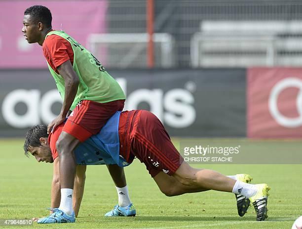 Bayern Munich's Austrian defender David Alaba sits on his teammate Bayern Munich's Spanish midfielder Xabi Alonso during a training session of the...