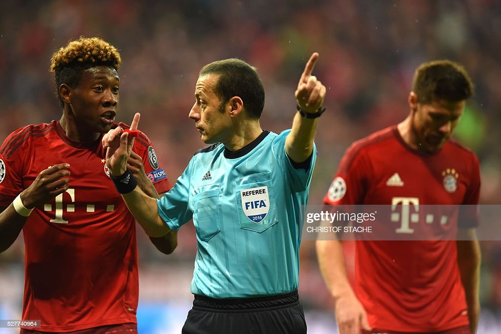 Bayern Munich's Austrian midfielder David Alaba (L) argues with Turkish referee Cuneyt Cakir (C) during the UEFA Champions League semi-final, second-leg football match between FC Bayern Munich and Atletico Madrid in Munich, southern Germany, on May 3, 2016. / AFP / Christof Stache