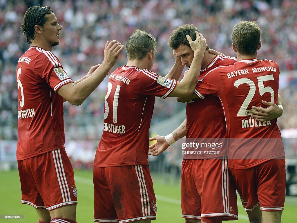 Bayern Munich's Belgian defender Daniel van Buyten, Bayern Munich's midfielder Bastian Schweinsteiger, Bayern Munich's Croatian striker Mario Mandzukic and Bayern Munich's striker Thomas Mueller celebrate scoring during the German first division Bundesliga football match FC Bayern Munich vs Hertha Berlin on October 26, 2013 in Munich, southern Germany.