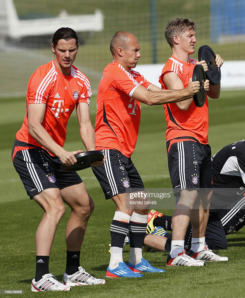 Bayern Munich's Belgian defender Daniel Van Buyten (L), Dutch midfielder Arjen Robben (C) and German midfielder Bastian Schweinsteiger (R) attend a training session at the Aspire Academy for Sports Excellence in Doha on January 6, 2013. Bayern Munich is in Qatar for a week-long training camp before the beginning of the new season of the German Bundesliga after the winter break.