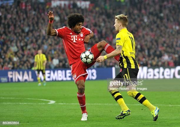 Bayern Munich's Bonfim Dante fouls Borussia Dortmund's Marco Reus resulting in a penalty for Borussia Dortmund