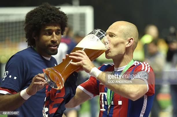 Bayern Munich's Brazilian defender Dante and Bayern Munich's Dutch midfielder Arjen Robben celebrate with a beer winning the DFB German Cup final...