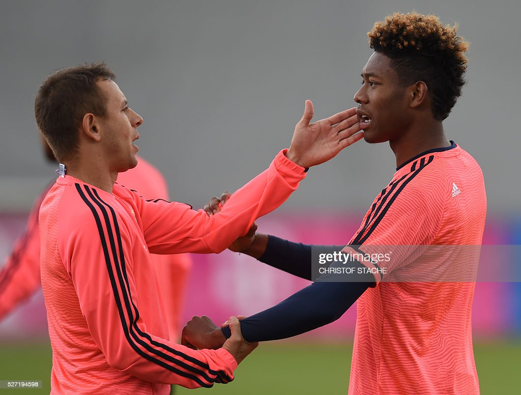 Bayern Munich's Brazilian defender Rafinha (L) and Bayern Munich's Austrian defender David Alaba (R) joke together during the final team training session one day prior to the Champions League semi-final, second-leg football match between Bayern Munich and Atletico Madrid at the club trainings area in Munich, southern Germany, on May 2, 2016. / AFP / CHRISTOF