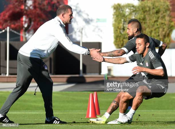 Bayern Munich's Brazilian defender Rafinha and Bayern Munich's Chilian midfielder Arturo Vidal train with fitness trainer Holger Broich during a...