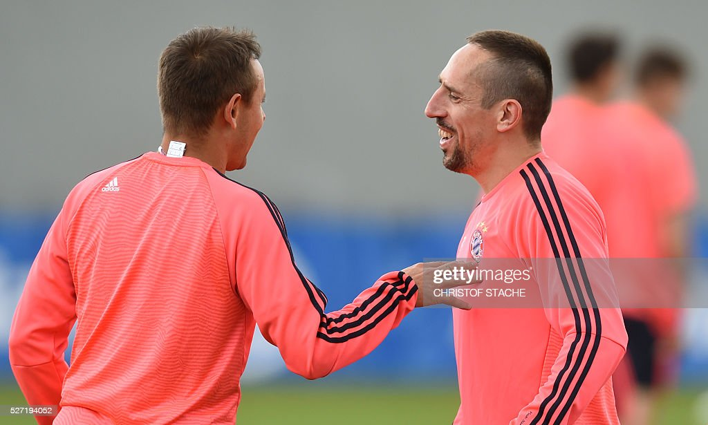 Bayern Munich's Brazilian defender Rafinha (L) and Bayern Munich's French midfielder Franck Ribery joke together during the final team training session one day prior to the Champions League semi-final, second-leg football match between Bayern Munich and Atletico Madrid at the club trainings area in Munich, southern Germany, on May 2, 2016. / AFP / CHRISTOF