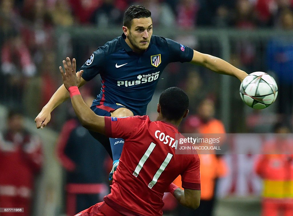 Bayern Munich's Brazilian midfielder Douglas Costa (front) and Atletico Madrid's midfielder Saul Niguez vie for the ball during the UEFA Champions League semi-final, second-leg football match between FC Bayern Munich and Atletico Madrid in Munich, southern Germany, on May 3, 2016. / AFP / John MACDOUGALL