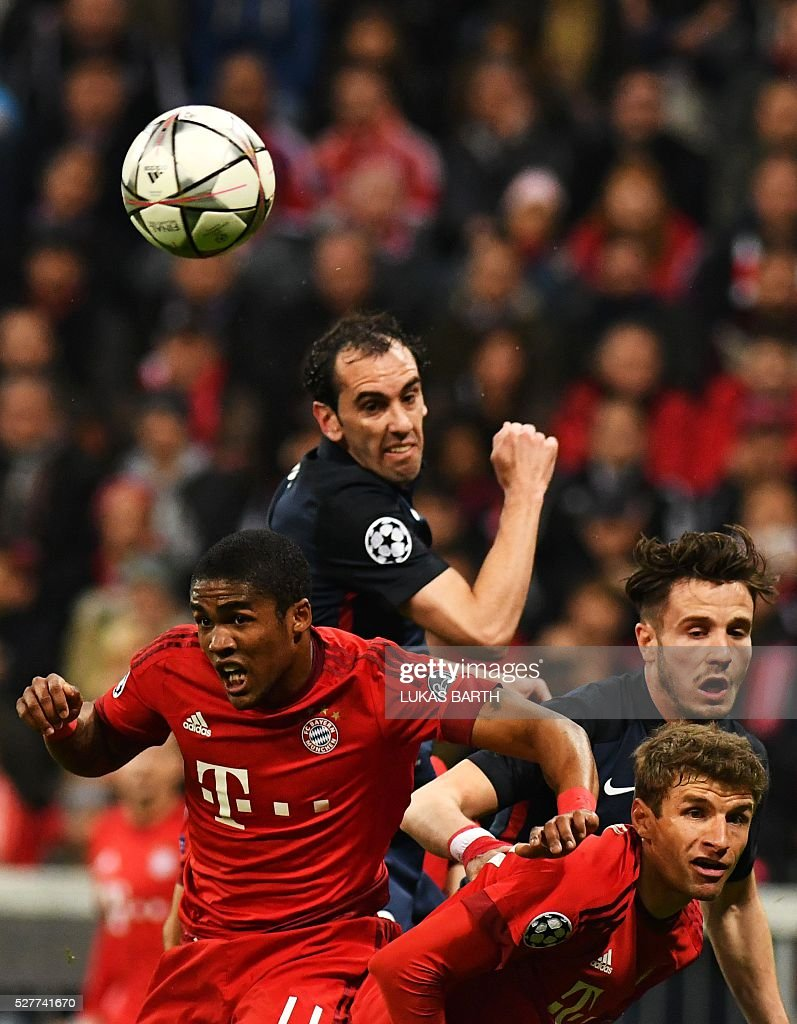 Bayern Munich's Brazilian midfielder Douglas Costa, Atletico Madrid's Uruguayan defender Diego Godin, Atletico Madrid's Uruguayan defender Jose Maria Gimenez and Bayern Munich's midfielder Thomas Mueller vie for the ball during the UEFA Champions League semi-final, second-leg football match between FC Bayern Munich and Atletico Madrid in Munich, southern Germany, on May 3, 2016. / AFP / LUKAS