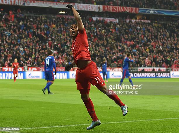 Bayern Munich's Brazilian midfielder Douglas Costa celebrates after his goal during the UEFA Champions League Group F football match between FCB...