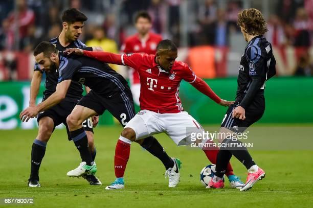 Bayern Munich's Brazilian midfielder Douglas Costa Madrid's Spanish defender Dani Carvajal and Madrid's Croatian midfielder Luka Modric vie for the...