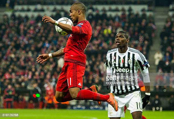 Bayern Munich's Brazilian midfielder Douglas Costa meets a pass watched by Juventus French midfielder Paul Labile Pogba during the UEFA Champions...