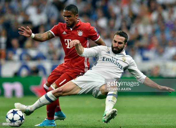 Bayern Munich's Brazilian midfielder Douglas Costa vies with Real Madrid's defender Dani Carvajal during the UEFA Champions League quarterfinal...