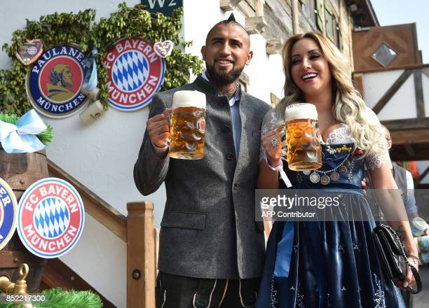 Bayern Munich's Chilean midfielder Arturo Vidal and his wife Maria Teresa Matus hold beer mugs as they pose during the traditional visit of members...