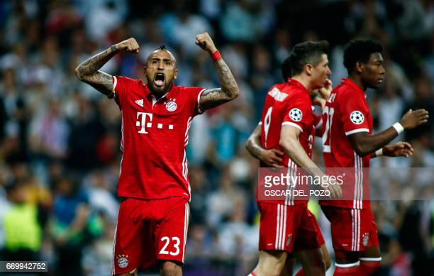 Bayern Munich's Chilean midfielder Arturo Vidal celebrates an own goal by Real Madrid during the UEFA Champions League quarterfinal second leg...