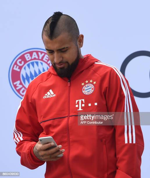 Bayern Munich's Chilean midfielder Arturo Vidal checks his mobile phone during a car handover event at the Audi headquarters in Ingolstadt southern...
