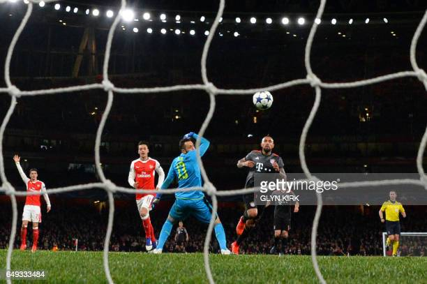 Bayern Munich's Chilean midfielder Arturo Vidal chips past Arsenal's Colombian goalkeeper David Ospina to score their fourth goal during the UEFA...