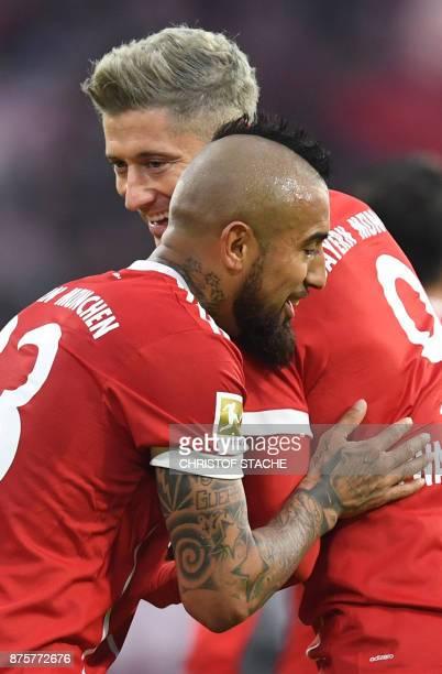 Bayern Munich's Chilean midfielder Arturo Vidal embraces his teammate Bayern Munich's Polish forward Robert Lewandowski after the second goal for...