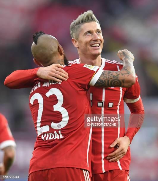 Bayern Munich's Chilean midfielder Arturo Vidal embraces his teammate Polish striker Robert Lewandowski during the German first division Bundesliga...