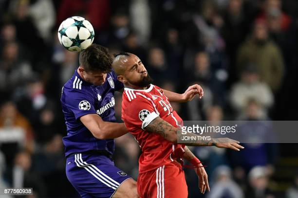 Bayern Munich's Chilean midfielder Arturo Vidal heads the ball with Anderlecht's Belgian midfielder Leander Dendoncker during the UEFA Champions...