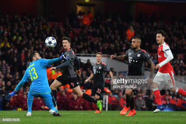 Bayern Munich's Chilean midfielder Arturo Vidal scores their fourth goal past Arsenal's Colombian goalkeeper David Ospina during the UEFA Champions...