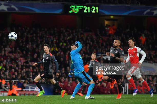 TOPSHOT Bayern Munich's Chilean midfielder Arturo Vidal scores their fourth goal past Arsenal's Colombian goalkeeper David Ospina during the UEFA...