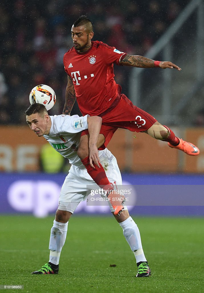 Bayern Munich's Chilian midfielder Arturo Vidal (R) and Augsburg's midfielder Dominik Kohr vie for the ball during the German first division Bundesliga football match of FC Augsburg vs FC Bayern Munich in Augsburg, southern Germany, on February 14, 2016. / AFP / CHRISTOF STACHE /