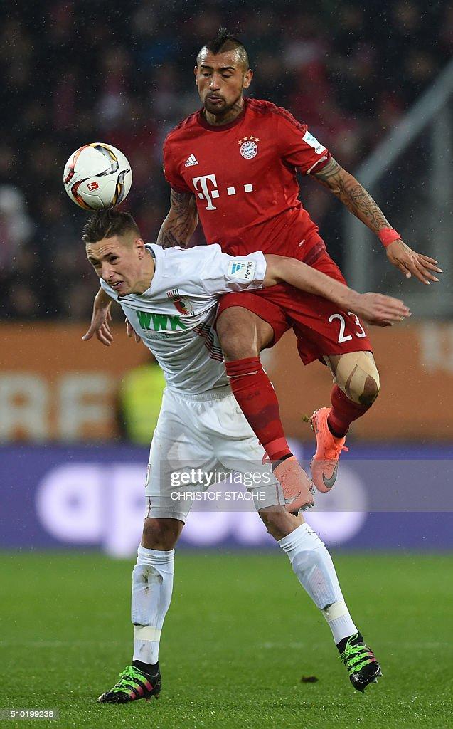 Bayern Munich's Chilian midfielder Arturo Vidal (R) and Augsburg's midfielder Dominik Kohr vie for the ball during the German first division Bundesliga football match of FC Augsburg vs FC Bayern Munich in Augsburg, southern Germany, on February 14, 2016. / AFP / CHRISTOF STACHE /
