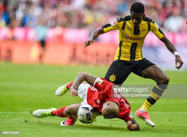 Bayern Munich's Chilian midfielder Arturo Vidal and Dortmund's French striker Ousmane Dembele vie for the ball during the German first division...