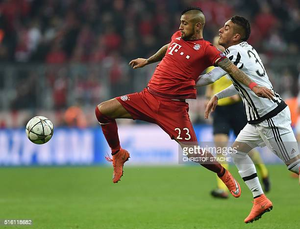 Bayern Munich's Chilian midfielder Arturo Vidal and Juventus Argentinian midfielder Roberto Pereyra vie for the ball during the UEFA Champions League...