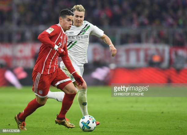 Bayern Munich's Colombian James Rodriguez and Hanover's midfielder Felix Klaus vie for the ball the German First division Bundesliga football match...