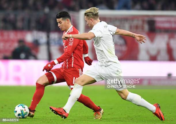 Bayern Munich's Colombian James Rodriguez and Hanover's midfielder Felix Klaus vie for the ball during the German First division Bundesliga football...
