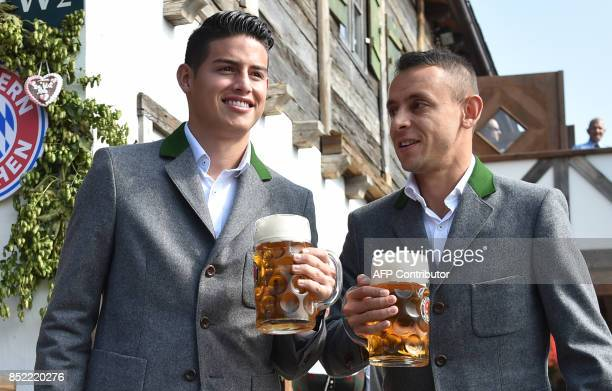Bayern Munich's Colombian midfielder James Rodriguez and Bayern Munich's Brazilian defender Rafinha hold beer mugs as they pose during the...