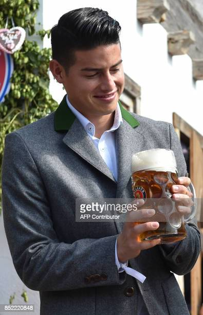 Bayern Munich's Colombian midfielder James Rodriguez holds a beer mug as he poses during the traditional visit of members of German first division...