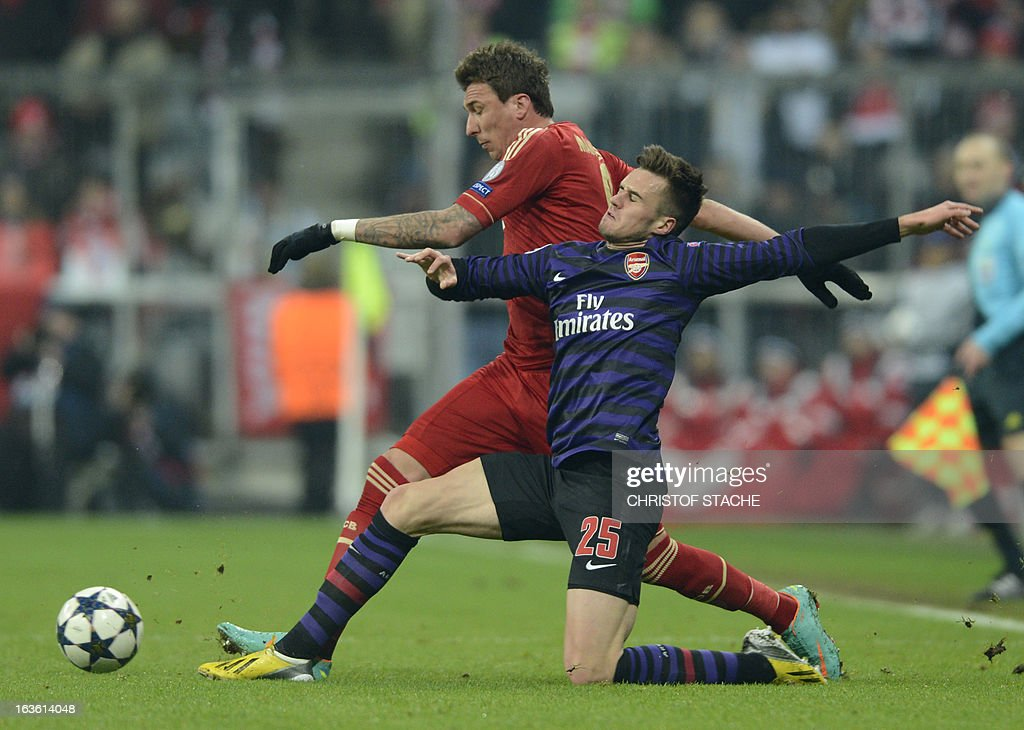 Bayern Munich's Croatian striker Mario Mandzukic (L) and Arsenal´s defender Carl Jenkinson vie for the ball during the UEFA Champions League Round of 16 second-leg football match FC Bayern Munich vs FC Arsenal London in Munich, southern Germany, on March 13, 2013.