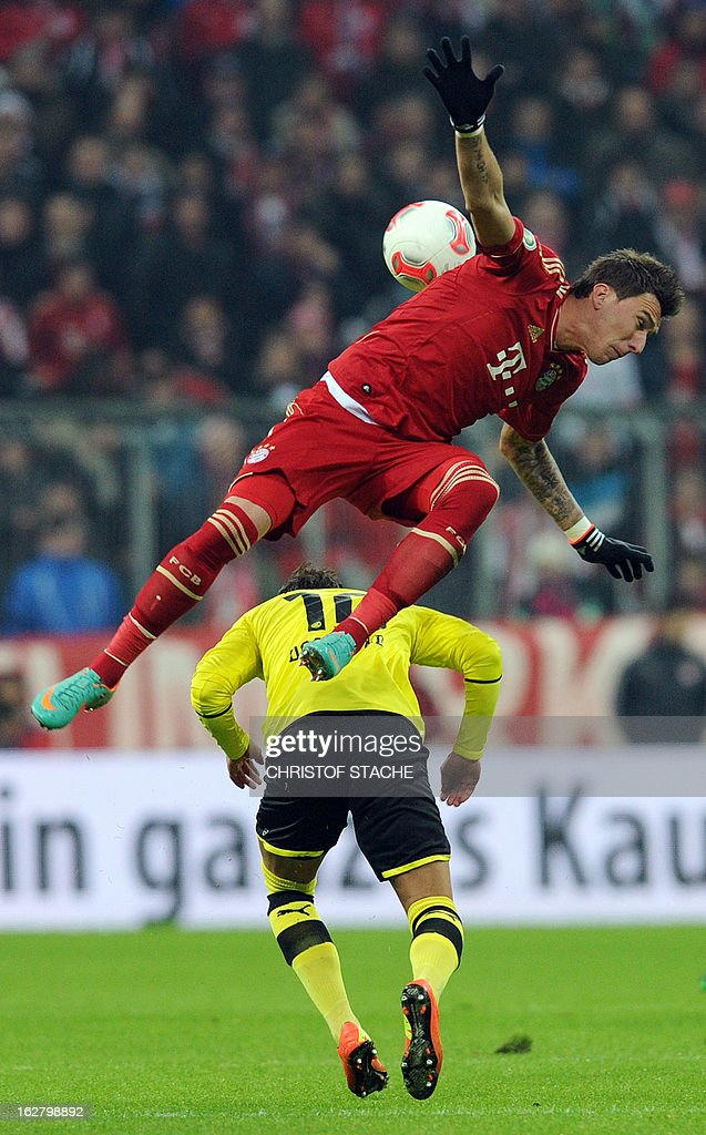 Bayern Munich's Croatian striker Mario Mandzukic (top) and Dortmund's midfielder Marco Reus vie for the ball during the German Cup quarter-final football match FC Bayern Munich vs Borussia Dortmund in Munich, southern Germany, on February 27, 2013. AFP PHOTO / CHRISTOF STACHE DURING THE MATCH AND PROHIBITS MOBILE (MMS) USE