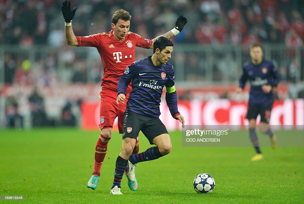 Bayern Munich's Croatian striker Mario Mandzukic (L) fights for the ball with Arsenal´s Spanish midfielder Mikel Arteta (L) during the UEFA Champions League Round of 16 second-leg football match FC Bayern Munich vs FC Arsenal London in Munich, southern Germany, on March 13, 2013. AFP PHOTO / ODD ANDERSEN