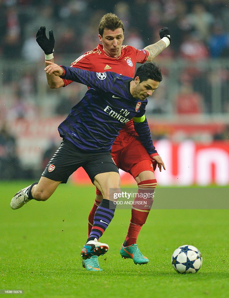 Bayern Munich's Croatian striker Mario Mandzukic fights for the ball with Arsenal´s Spanish midfielder Mikel Arteta (front) during the UEFA Champions League Round of 16 second-leg football match FC Bayern Munich vs FC Arsenal London in Munich, southern Germany, on March 13, 2013. AFP PHOTO / ODD ANDERSEN