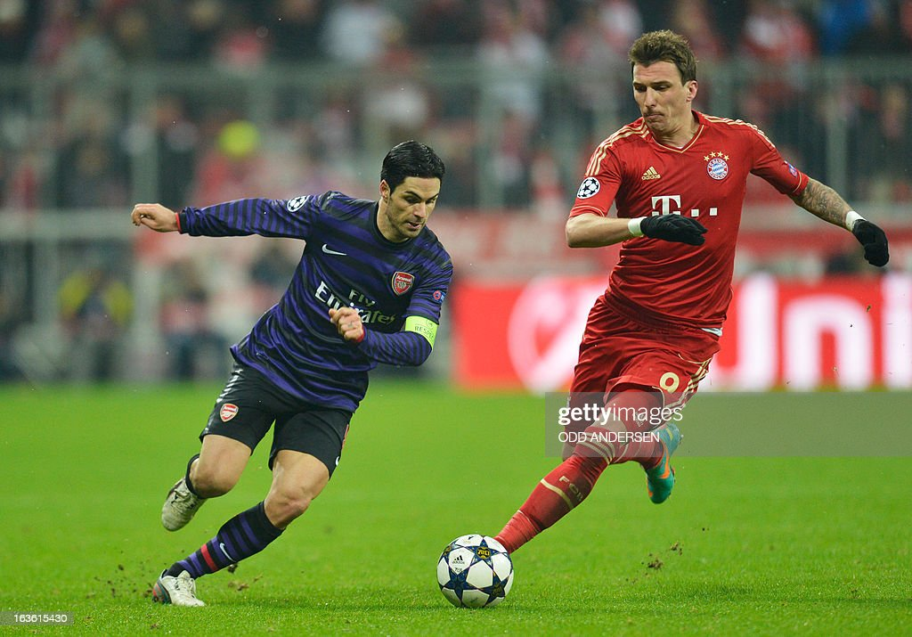 Bayern Munich's Croatian striker Mario Mandzukic fights for the ball with Arsenal´s Spanish midfielder Mikel Arteta (L) during the UEFA Champions League Round of 16 second-leg football match FC Bayern Munich vs FC Arsenal London in Munich, southern Germany, on March 13, 2013. AFP PHOTO / ODD ANDERSEN
