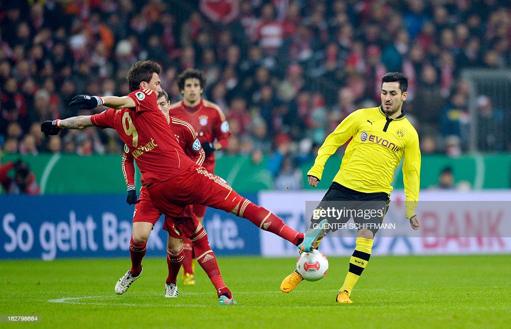 Bayern Munich's Croation striker Mario Mandzukic and Dortmund's German midfielder Ilkay Guendogan (R) vie for the ball during the German Cup quarter-final football match FC Bayern Munich vs Borussia Dortmund in Munich, southern Germany, on February 27, 2013. AFP PHOTO / GUENTER SCHIFFMANN DURING THE MATCH AND PROHIBITS MOBILE (MMS) USE DURING AND FOR FURTHER TWO HOURS AFTER THE MATCH. FOR MORE INFORMATION CONTACT DFL.