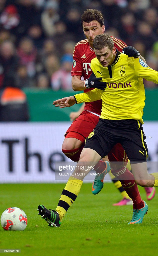 Bayern Munich's Croation striker Mario Mandzukic and Dortmund's German midfielder Sven Bender (R) vie for the ball during the German Cup quarter-final football match FC Bayern Munich vs Borussia Dortmund in Munich, southern Germany, on February 27, 2013. AFP PHOTO / GUENTER SCHIFFMANN DURING THE MATCH AND PROHIBITS MOBILE (MMS) USE