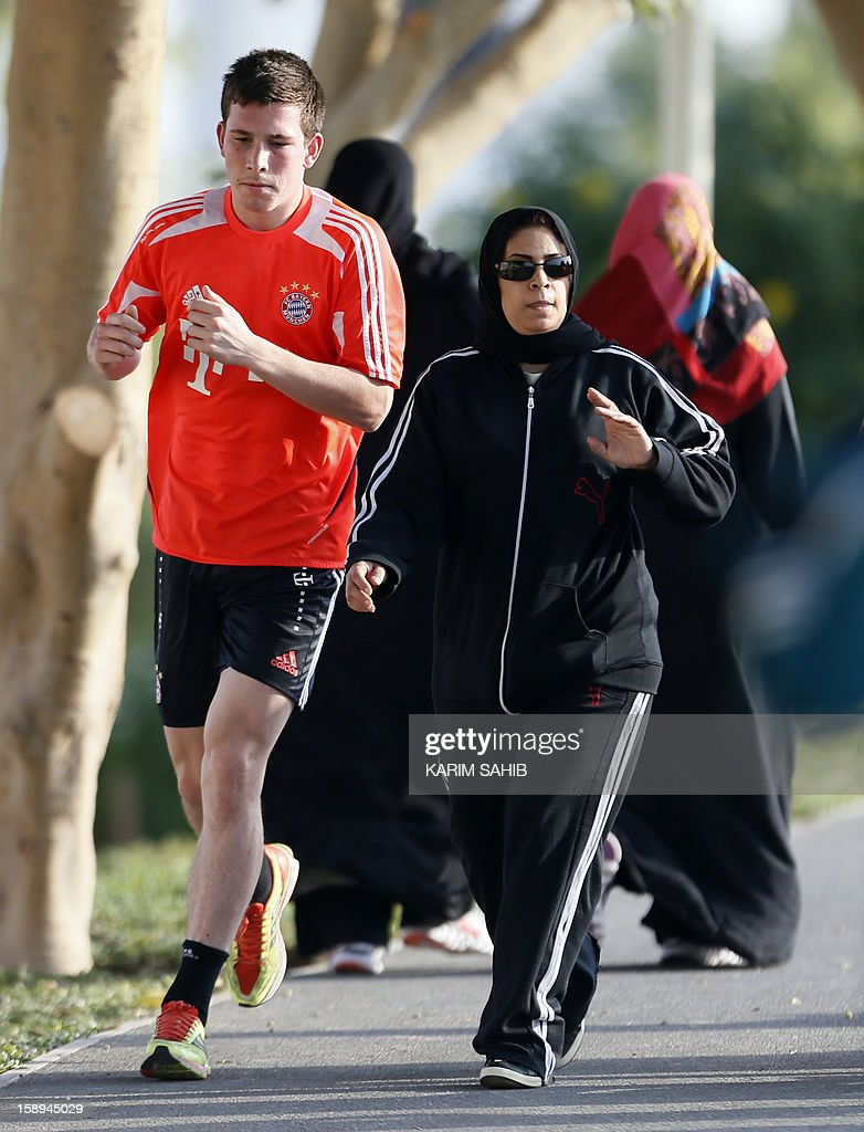 Bayern Munich's Danish defender Pierre-Emile Hojbjerg (L) runs past a veiled women during a training session at Aspire Academy for Sports Excellence on January 4, 2013 in Doha. Bayern Munich is in Qatar for a week-long training camp before the beginning of the new season of the German Bundesliga after the winter break. AFP PHOTO/KARIM SAHIB