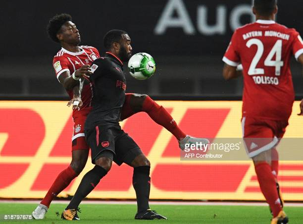 Bayern Munich's defender David Alaba and Arsenal forward Alexandre Lacazette vie for the ball during the International Champions Cup football match...